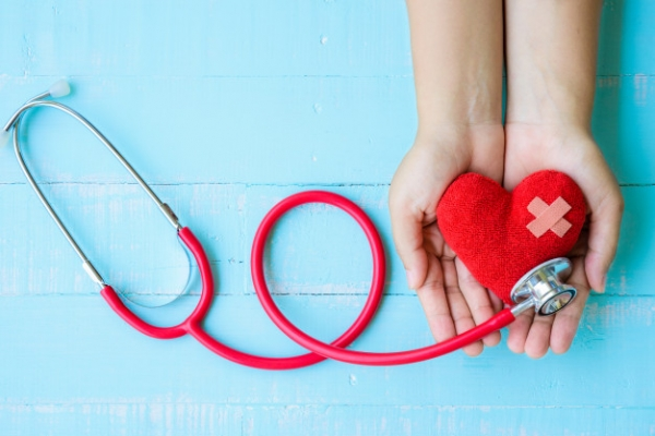 woman-hand-holding-red-heart-with-stethoscope-blue-wooden-background_53476-356