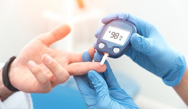 Doktor kan şekeri seviyesini glukometre ile kontrol ediyor